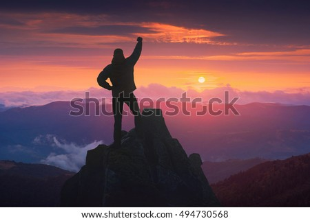 Man standing on a cliffs edge with raised hand against colorful sunset in a mountain valley.