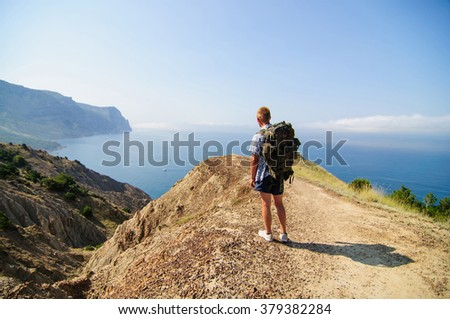 man standing on a hill near the sea