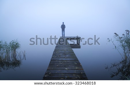 Man standing on a jetty, looking over a lake during a foggy, autumn morning. - stock photo