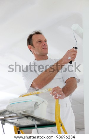 Man standing on a ladder and painting a wall - stock photo