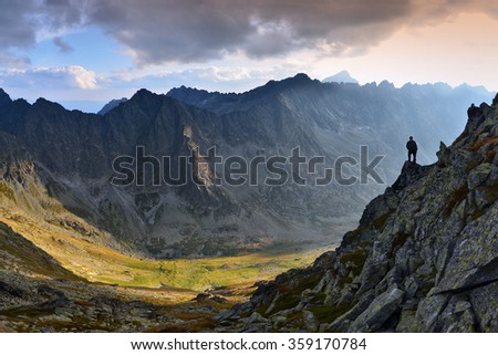 Man standing on a ledge of a mountain, enjoying the beautiful sunset over a wide river valley in Slovakia - stock photo