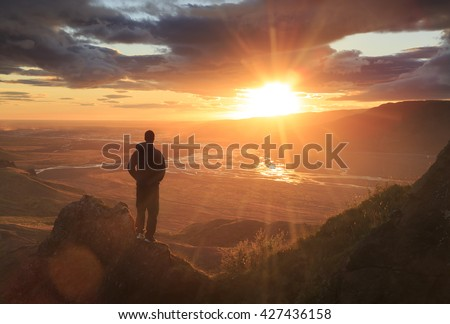 Man standing on a ledge of a mountain, enjoying the sunset over a river valley in Thorsmork, Iceland. With lens flare.