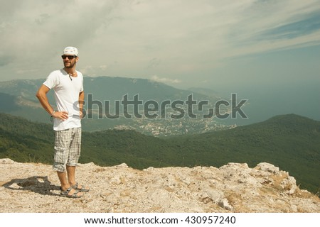 man standing on a mountain against the sky - stock photo