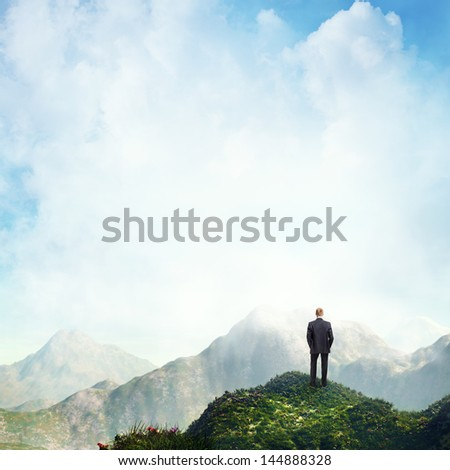 man standing on a peak - stock photo