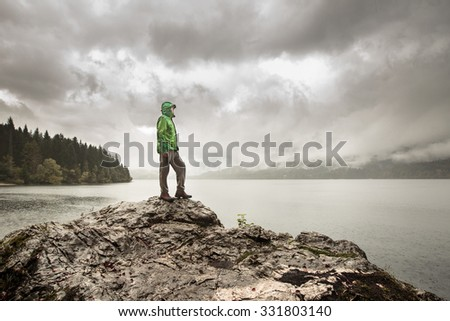 Man standing on a rock beside a dramatic mountain lake after a hike in the rainy, gloomy day. Active lifestyle, outdoor activities, moods and emotions concept.  - stock photo