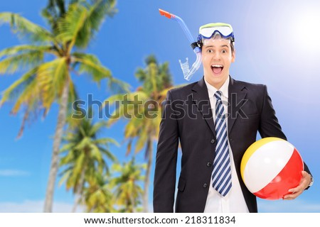 Man standing on beach with snorkel and beach ball - stock photo