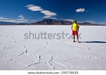 Man standing on Bonneville salt flats and looking to horizon - USA - stock photo