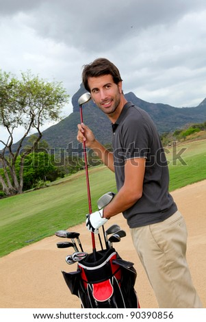 Man standing on golf course with equipment - stock photo
