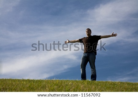 Man standing on Grass with his arms wide open - freedom concept