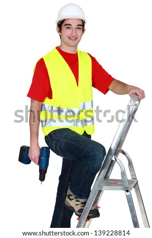 Man standing on ladder with drill - stock photo