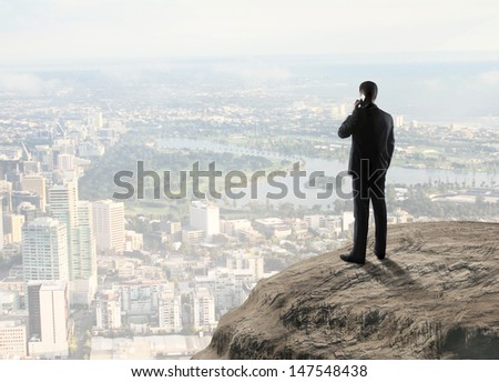 man standing on rock with phone - stock photo