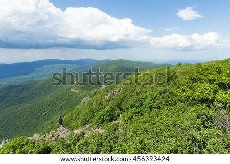 Man standing on rocky outlook viewpoint over lush green forest in Shenandoah National Park, Virginia, USA  - stock photo