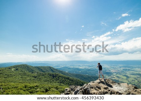 Man standing on rocky outlook viewpoint taking photo of lush green forest in Shenandoah National Park, Virginia, USA - stock photo