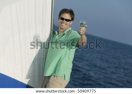 Man standing on sailboat, toasting with glass of white wine, (portrait)