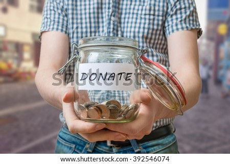 Man standing on street is collecting donations in jar. - stock photo