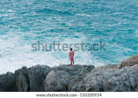 Man standing on the cliff on the shore of the ocean