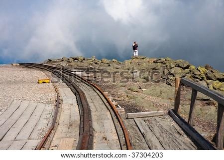 Man standing on the edge atop Mount Washington - stock photo