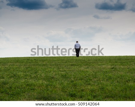 man standing on the edge of a countryside, looking at the sky, contemplating, alone, abandoned, symbolic concept