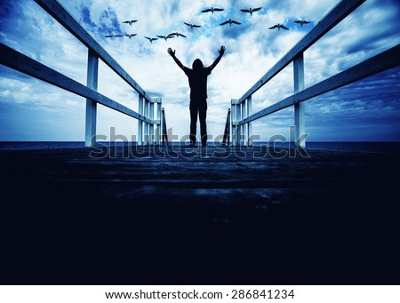 man standing on the edge of pier with hand open wide,freedom concept,inspiration and joy  - stock photo