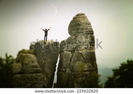 man standing on the mountain during a solar eclipse. Cesky raj sandstone cliffs - Prachovske skaly, Czech Republic - stock photo