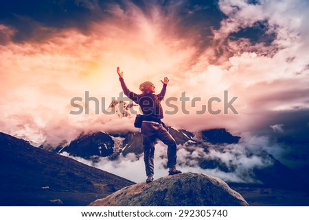 Man standing on the stone with hands up. Trekking in Nepal