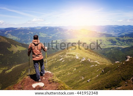 Man standing on the top of the mountain - stock photo