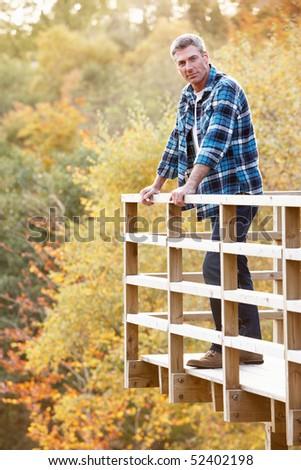 Man Standing On Wooden Balcony Overlooking Autumn Woodland - stock photo