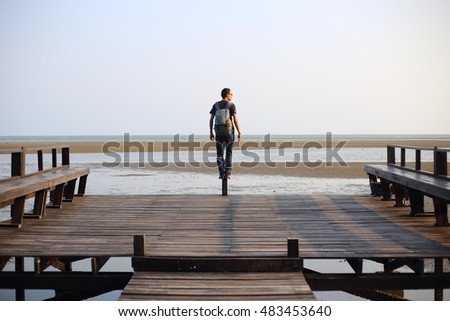man standing on wooden pier