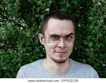 Man standing outdoors in front of green foliage raising an eyebrow in total disbelief and distrust glaring at the camera with an intense stare - stock photo