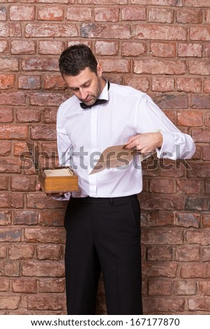 Man standing reading a old document from a wooden box which he is holding in his hand while standing in front of a brick wall