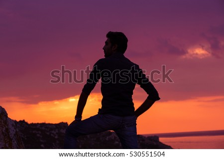 man standing thinking back light sunset lighting side view profile silhouette summer evening beach
