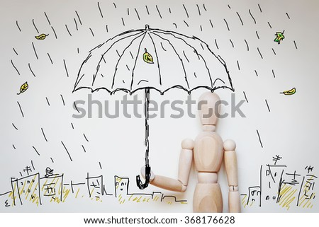 Man standing under umbrella in raining. Abstract image with wooden puppet - stock photo