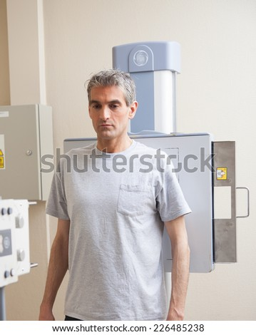 Man standing undergoing x-ray scan. - stock photo