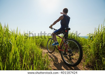Man standing with a bicycle on the path with green grass