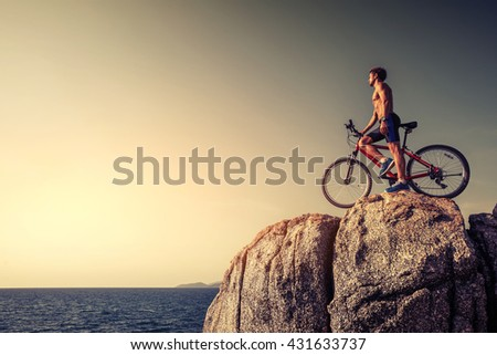 Man standing with a bicycle on the rock during sunset
