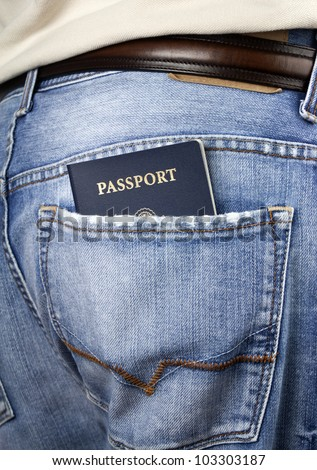 Man standing with American blue passport in back pocket of denim blue jeans with copy space.