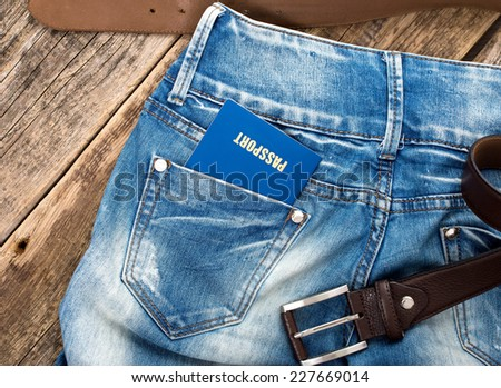 Man standing with American blue passport in back pocket of denim blue jeans with copy space. - stock photo