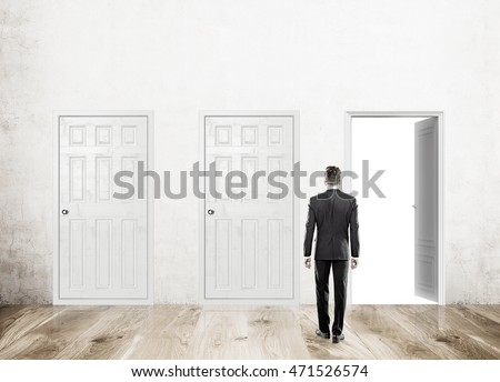 Man standing with back to camera in corridor with three doors, one open. Wood floor. Concept of decision made. Mock up