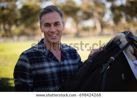 Man standing with horse in the ranch on a sunny day