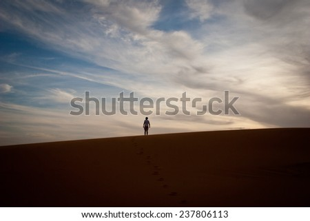Man stands alone, on a dune in the Sahara Desert
