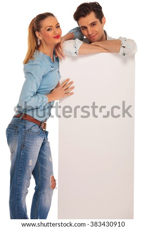 man stands behind white blank billboard with hands crossed while woman rests her arm on his shoulder. both are looking at the camera in isolated studio background. - stock photo