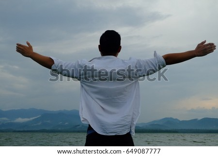 Man stands hugging the sky
