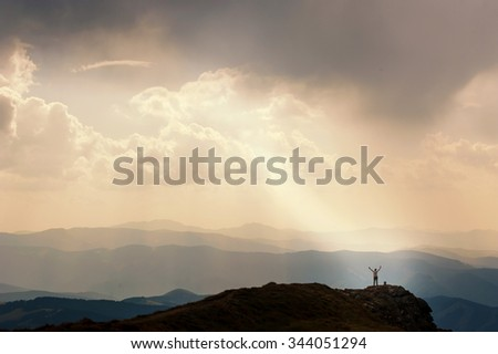 Man stands near the cross on top of mountain