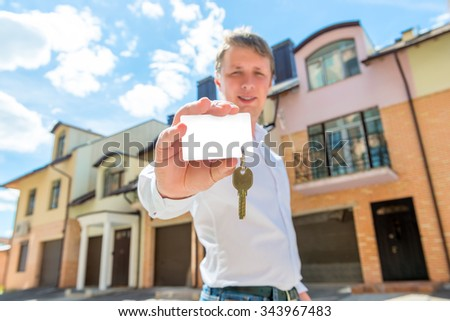 man stands near the house and shows the key to the apartment