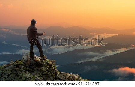 Man stands on background of mountains at sunset