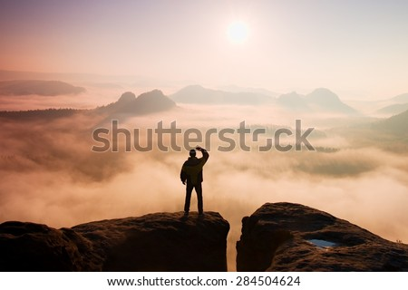Man stands on the peak of sandstone rock in national park Saxony Switzerland and watching to Sun. Beautiful moment the miracle of nature. Morning mountain background. Man watch foggy miracle.