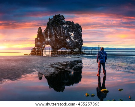 Man stands on the surface of water at fall of tide and and admiring of sunrise. Huge basalt stack Hvitserkur on the eastern shore of the Vatnsnes peninsula, Iceland, Europe.