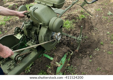 Man  start  tractor cultivator in the garden - stock photo