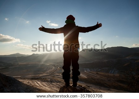 Man staying against the sun with open arms  - stock photo
