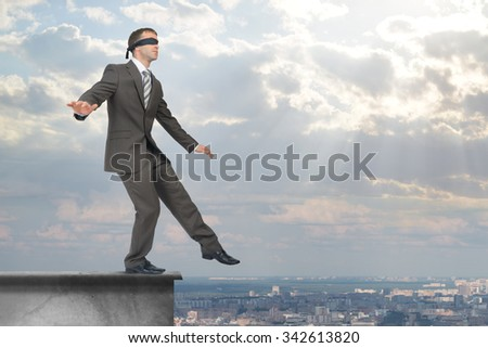 Man stepping from edge of building roof with band on his eyes